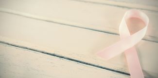 Close-up of pink Breast Cancer Awareness ribbon on table. Close-up of pink Breast Cancer Awareness ribbon on white wooden table royalty free stock images