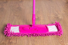 Close up of pink cleaning mop on wooden floor Stock Images