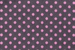 Pink dots over purple polka dot fabric background and texture. Close up of Pink dots over purple polka dot fabric background and texture. Hi res Stock Image