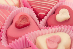 Close-up of a pink heart shaped petit fours cakes seen from the side. On a pink background Stock Images
