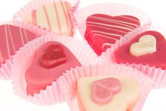 Close-up of a pink heart shaped petit fours cakes seen from the side. On a white background Royalty Free Stock Photos
