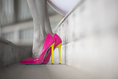 Close up pink high heel shoes woman legs filtered image. Concept detail of woman sitting in Elegant sexy pink high heel shoes, relaxed on bench, copy space Stock Photo