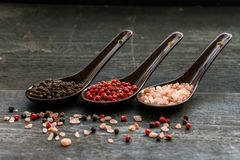 Close up pink himalayan salt and peppers in spoons. Studio shot of three spoons with rough pink salt, black and pink peppercorns on dark wooden background Royalty Free Stock Photos