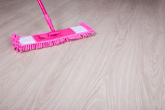 Close up of pink mop on wooden floor Royalty Free Stock Images