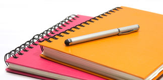 Close-up of pink orange note book and pen Stock Images