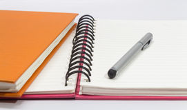Close-up of pink, orange open note book and pen Stock Photography