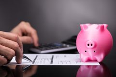 Close-up Of Pink Piggy Bank Upside Down. Pink Piggy Bank Upside Down Besides Businessperson Calculating Invoice royalty free stock photos