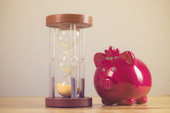 Close-up of a pink porcelain piggy bank with a vintage hourglass Royalty Free Stock Images
