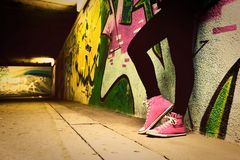 Close up of pink sneakers worn by a teenager. Grunge graffiti wall, retro vintage style Royalty Free Stock Images