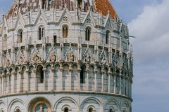 Close-up of the Pisa Baptistry under sky and clouds, in the Cathedral Square of Pisa, Italy royalty free stock images