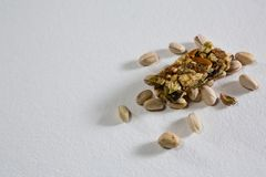 Pistachio and granola bar on white background Royalty Free Stock Photography