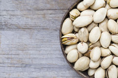 Close up of pistachio nuts. On wood table background Royalty Free Stock Photo