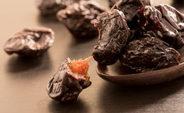 Close up of pitted prunes on black color wooden spoon. Close up of pitted prunes on black color wooden spoon stock image
