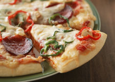 Close up of Pizza with the cut off slice Royalty Free Stock Photography
