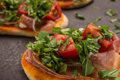 Close up pizza with ham, tomato and rucola Stock Images