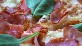 Close up. Pizza with tomatoes and cheese background rotating on the kitchen table