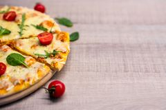 Close up of pizza with tomatoes and herbs over wooden table background with copy space stock photography