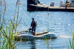 Close Up of Plants on Blurred Man Driving a Jet Boating. At Sea royalty free stock images
