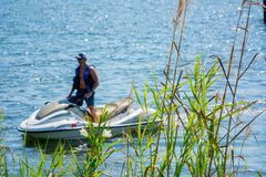 Close Up of Plants on Blurred Man Driving a Jet Boating. At Sea royalty free stock photos