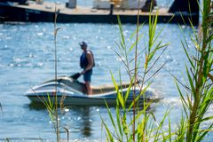 Close Up of Plants on Blurred Man Driving a Jet Boating. At Sea stock photos