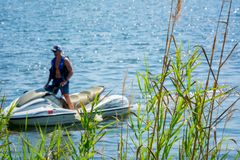 Close Up of Plants on Blurred Man Driving a Jet Boating. At Sea stock images