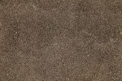 Close-up on a plastered wall. Warm gray and rough wall surface royalty free stock photography