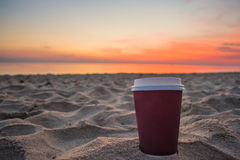 Close up plastic coffee cup on sand beach and view of sunset or sunrise background,peaceful Stock Photos