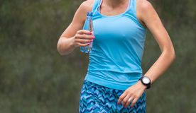 Close-up plastic water bottle in woman runner hand. girl preparing herself for marathon.