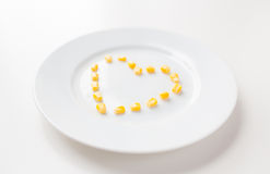 Close up of plate with corn in heart shape Royalty Free Stock Photography