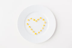 Close up of plate with corn  in heart shape Stock Images
