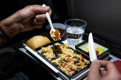 Close up of a plate of food served on the airplane. Man eating rice salad, bread, fruits, tea, and water on an airplane stock images