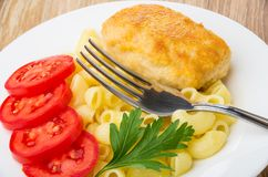 Close up of fried cutlet, pasta, slices of tomato Royalty Free Stock Photos