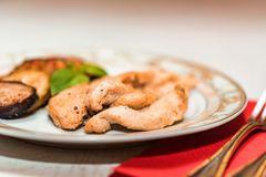 Pieces of roasted chicken and vegetables on plate. Close up plate with pieces of roasted chicken fillet and vegetables, healthy food concept. Selective focus Royalty Free Stock Photo