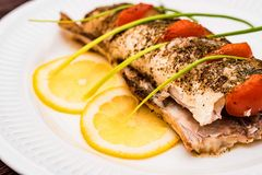 Roasted zander fillet with asparagus and lemon. Close up plate with pike perch fillet, lemon, tomato and asparagus. Healthy diet concept Royalty Free Stock Photos