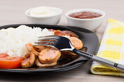 Close up of plate with rice, sausage, tomatoes, ketchup, mayonna Stock Images