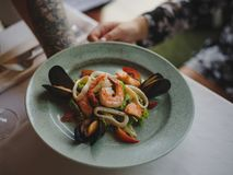 A close-up of a plate with seafood, a dinner service and a glass of wine in waiter`s hand on a white tablecloth. A beautiful dinner composition on a blurred Stock Images