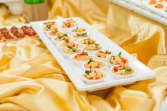 Close up plate with tartalets on catering table with dishes and snacks on the business event in the hotel hall. Service at busines Royalty Free Stock Image