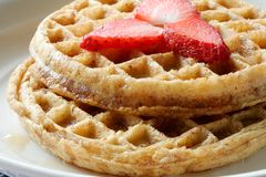 Close-up of a plate of waffles with strawberries. Close-up photo of two stacked waffles on a white plate with strawberries Stock Photography