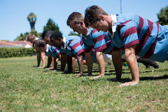 Close up of players doing push up at grassy field. On sunny day Stock Image