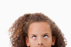 Close up of a playful girl looking above her. Against a white background Royalty Free Stock Image