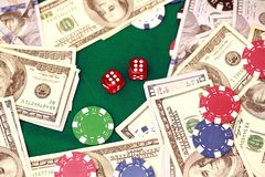 Close up of red dice, chips and cash on gambling table. Casino, gambling and entertainment concept royalty free stock photos
