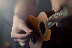 Close Up Playing Ukulele. Closeup shirtless male musician playing soprano ukulele Royalty Free Stock Photo