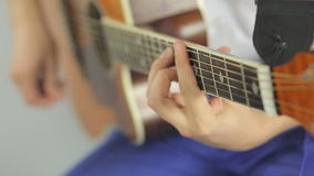Close-up of playing on a wooden guitar in the stock video footage