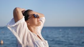 Close-up pleasant tanned relaxed girl in white shirt raising hand enjoying freedom at sea background