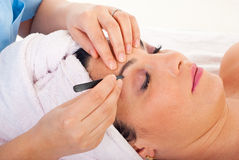 Close up of plucking eyebrows. Close up of beautician hands plucking woman eyebrows in a spa retreat stock image
