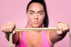 Close up of plumb mulatto woman showing body measuring tape Royalty Free Stock Image