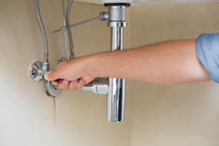 Close up of a plumber repairing washbasin Royalty Free Stock Images