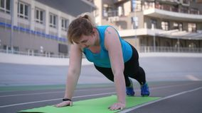 Overweight woman doing push ups on sports stadium. Close-up of plus size female in sportswear doing push-ups lying down on sports mat during fitness workout on stock video