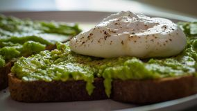 Close up of a poached egg on a smashed avocado toast with ground black pepper. Landscape format royalty free stock photos