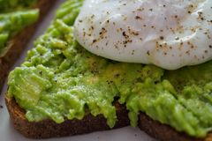 Close up of a poached egg on a smashed avocado toast with ground black pepper. Landscape format stock photos